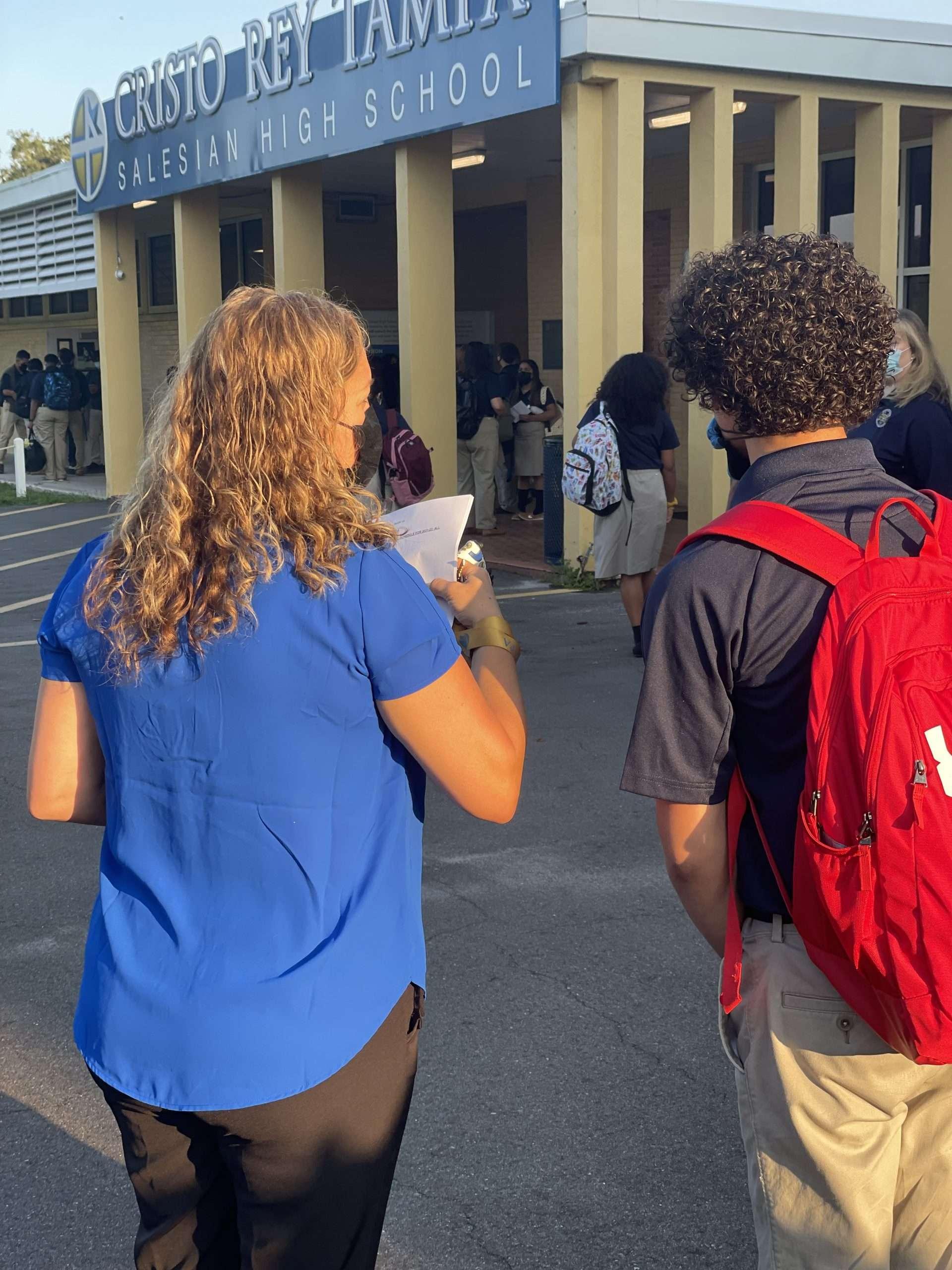 Registrar Mrs. Valero walking a student to class